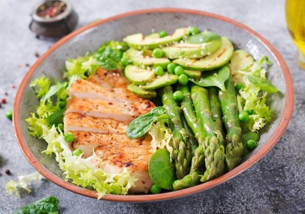 Filetto di pollo cotto su una griglia con contorno di asparagi e avocado alla griglia. salutare