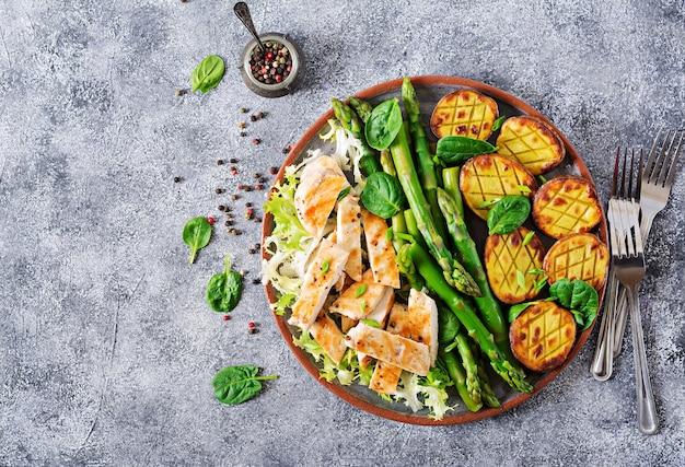 Filetto di pollo cotto su una griglia con contorno di asparagi e patate al forno. vista dall'alto