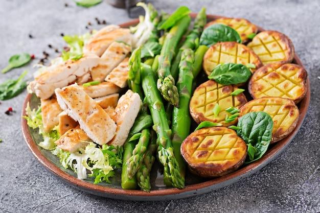 Filetto di pollo cotto su una griglia con contorno di asparagi e patate al forno.