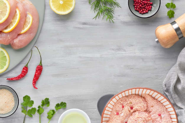 Filetto di pollo crudo. carne con pangrattato, erbe aromatiche, limone e olio da cucina, copia-spazio