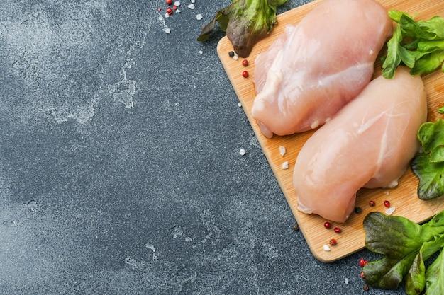 Filetto di pollo crudo con erbe e spezie su superficie scura con