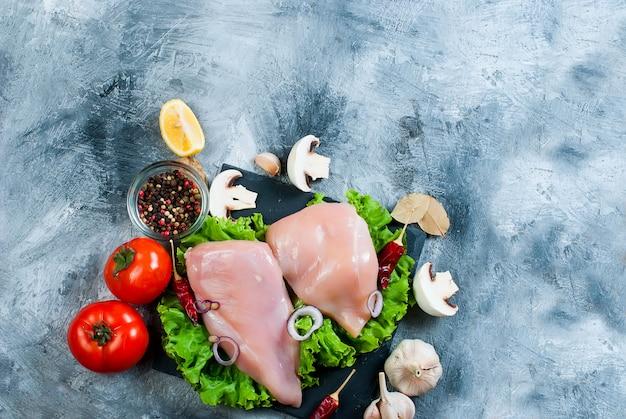 Filetto di pollo crudo sul tagliere con spezie ed erbe aromatiche.