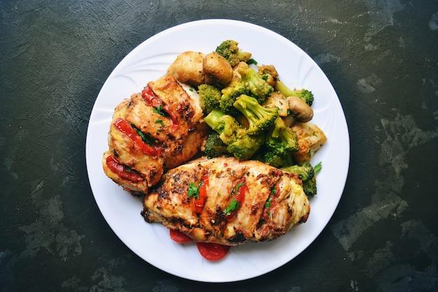 Filetto di pollo fritto. broccoli e cavolfiori. petto di pollo al forno. pollo e pomodoro alimento in un piatto bianco su un tavolo di cemento nero.