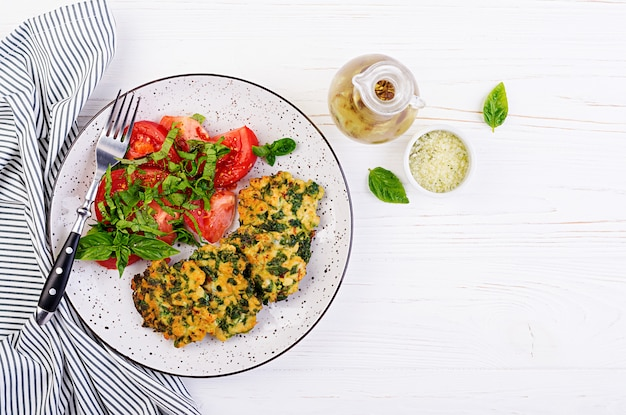 Filetto di pollo tritato con bistecca al forno con spinaci e contorno di insalata di pomodori. cucina europea. cibo dietetico. vista dall'alto