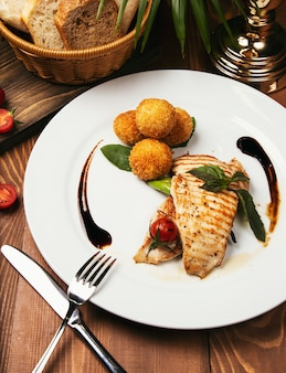 Filetto di salmone al forno con patate e panini al formaggio e verdure miste.