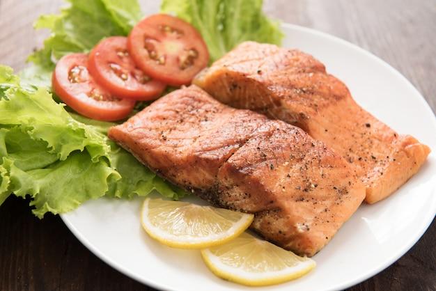 Filetto di salmone alla griglia cucinato barbecue e servito con erbe fresche e limone