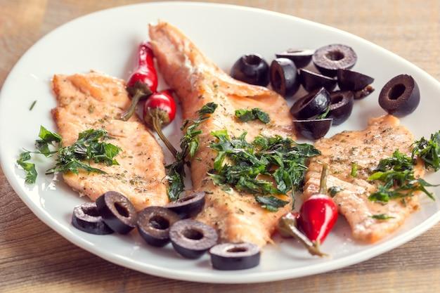 Filetto di salmone con olive, erbe aromatiche e peperoncino piccante