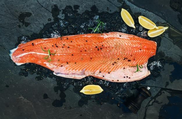 Filetto di salmone crudo con limone e rosmarino su ghiaccio scheggiato su fondale di pietra scura