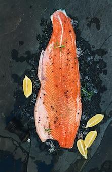 Filetto di salmone crudo con limone e rosmarino su ghiaccio scheggiato