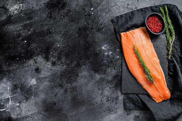 Filetto di salmone crudo con rosmarino e pepe rosa. pesce biologico. superficie nera. vista dall'alto. copia spazio
