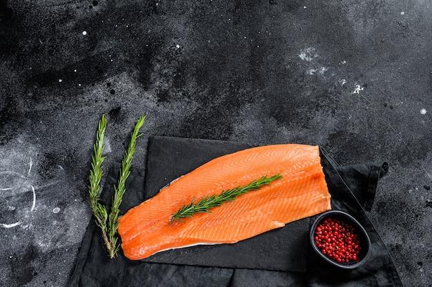 Filetto di salmone crudo con rosmarino e pepe rosa. pesce biologico. .