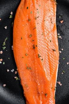 Filetto di salmone crudo con sale e peperoncino in una padella. pesce biologico.