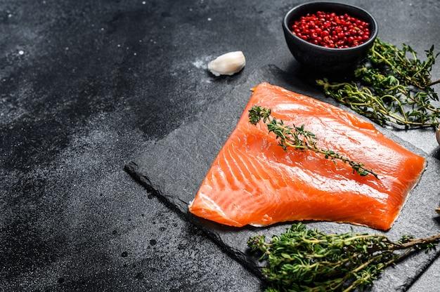 Filetto di salmone crudo fresco con timo sul nero. vista dall'alto. copia spazio