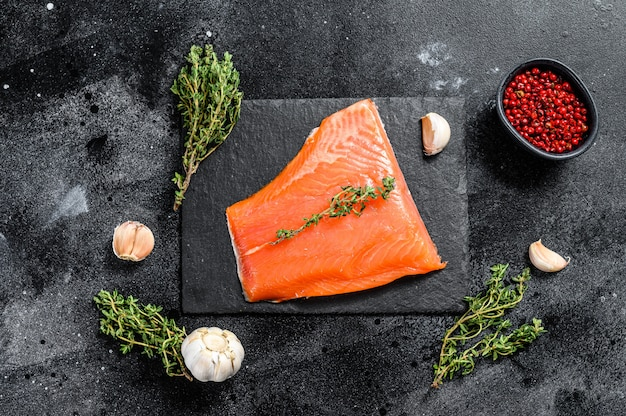 Filetto di salmone crudo fresco con timo sul nero. vista dall'alto