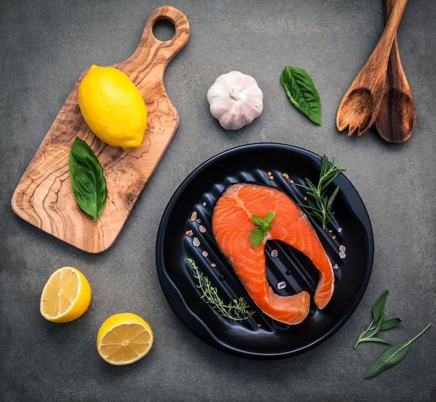 Filetto di salmone crudo nella piastra nera con ingredienti.