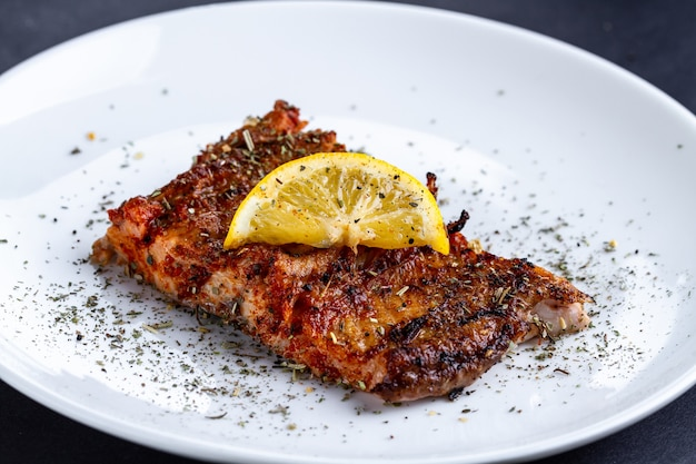 Filetto di salmone fresco e grigliato con una fetta di limone succoso, spezie ed erbe su un piatto bianco