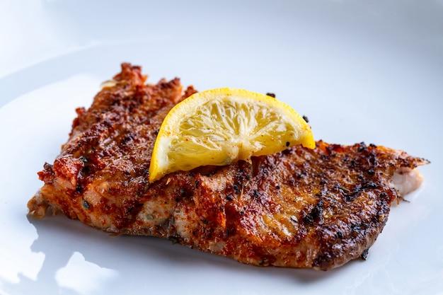 Filetto di salmone fresco e grigliato con una fetta di limone succoso su un piatto bianco