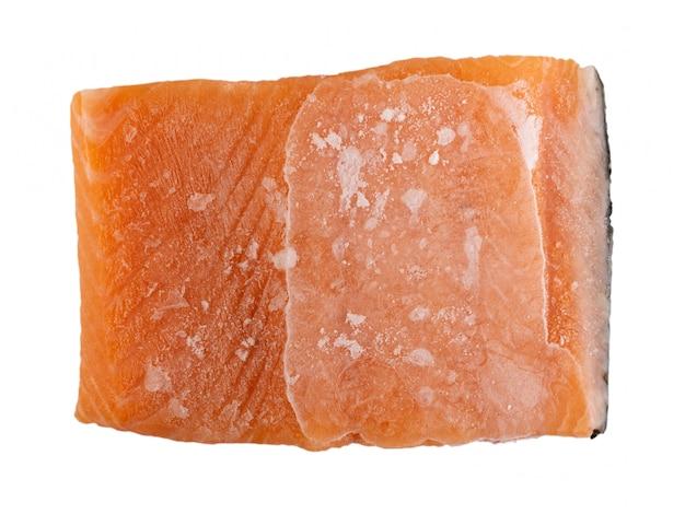 Filetto di salmone ghiacciato congelato isolato su priorità bassa bianca. pezzo spesso di trota rossa closup