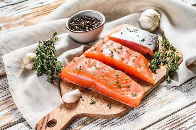 Filetto di salmone salato con timo su legno bianco. vista dall'alto