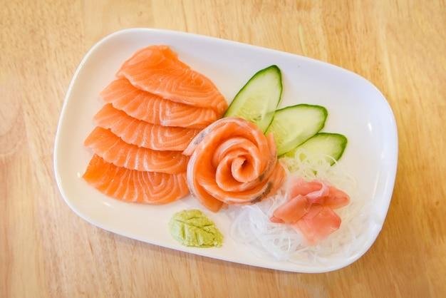 Filetto di salmone sashimi crudo con cibo giapponese e cetriolo di verdure e wasabi nel ristorante