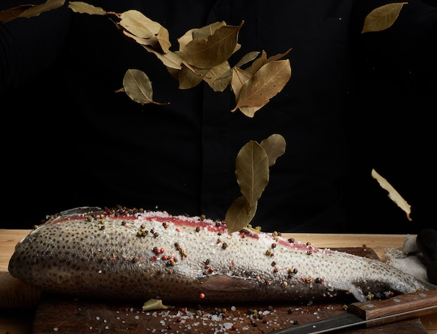 Filetto di salmone senza testa su una tavola di legno cosparsa di foglie di alloro secco
