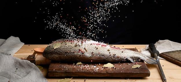 Filetto di salmone senza testa su una tavola di legno cosparsa di grande sale bianco e pepe