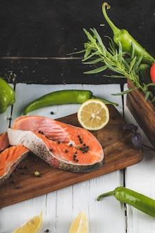 Filetto di salmone sulla tavola di legno con limone e rosmarino