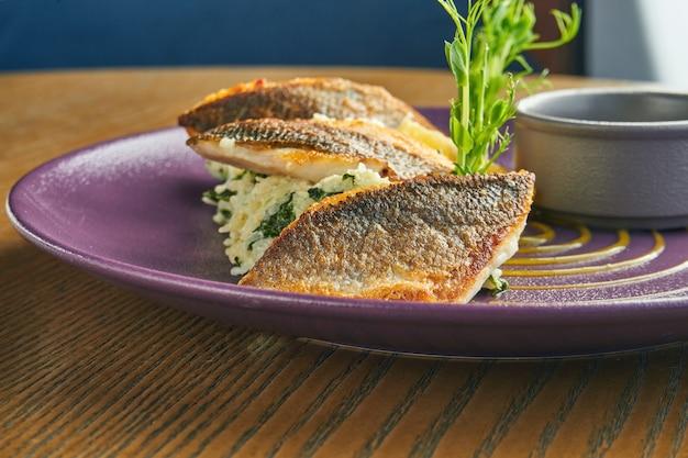 Filetto impanato fritto di branzino con contorno di riso su un piatto viola su un tavolo di legno. servizio al ristorante. primo piano, messa a fuoco selettiva
