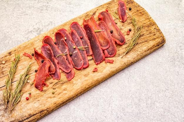 Filetto secco di carne di manzo con mix di pepe e rosmarino secco su tavola di legno vintage