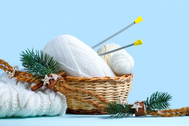 Fili bianchi per maglieria, ferri da maglia e un maglione lavorato a maglia bianco. concetto di maglieria. maglieria e abbigliamento invernale
