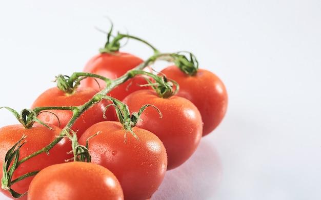 Filiale dei pomodori organici rossi su un bianco.