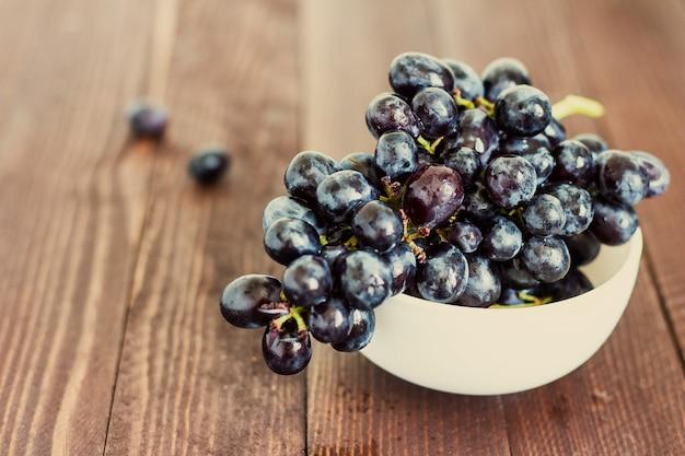 Filiale dell'uva nera in ciotola su legno scuro