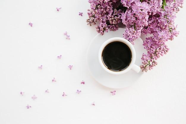 Filiale della tazza di caffè e del lillà su bianco