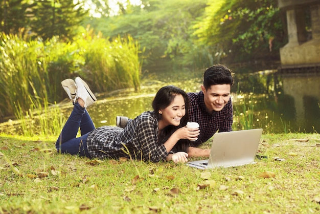 Film di sorveglianza delle coppie asiatiche attraenti sul computer portatile mentre trovandosi sull'erba verde