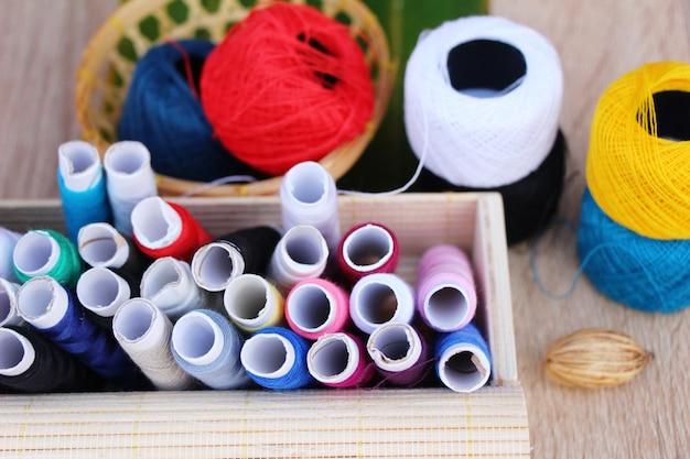 Filo colorato per cucire su fondo di legno