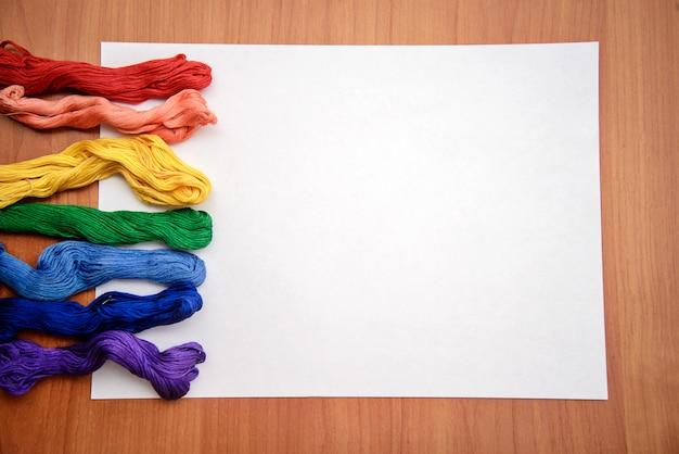 Filo da ricamo multicolore su un lenzuolo bianco