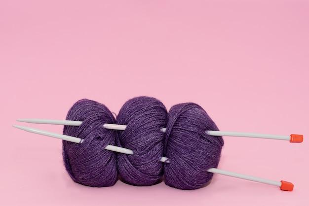 Filo di colore per maglieria, sciarpa lavorata a maglia, ferri da maglia su uno sfondo scuro.