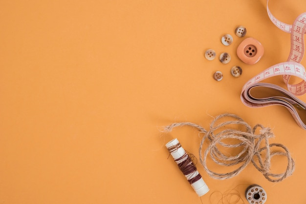 Filo di iuta; pulsante; misurazione nastro e bobina su sfondo colorato