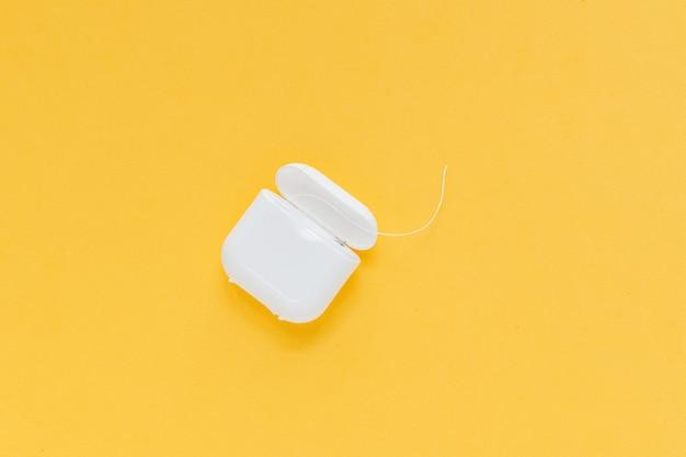 Filo interdentale di igiene dentale, disposizione piana del colluttorio, vista superiore, copyspace, giallo