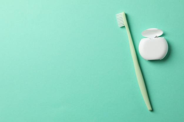 Filo interdentale e spazzolino da denti su sfondo menta, spazio per il testo