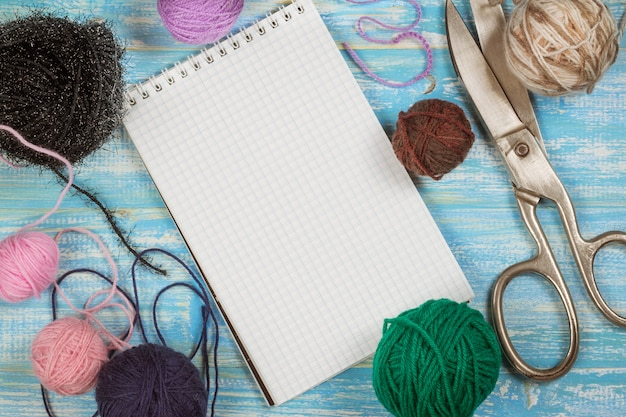 Filo multicolore con lana e forbici su un tavolo di legno.