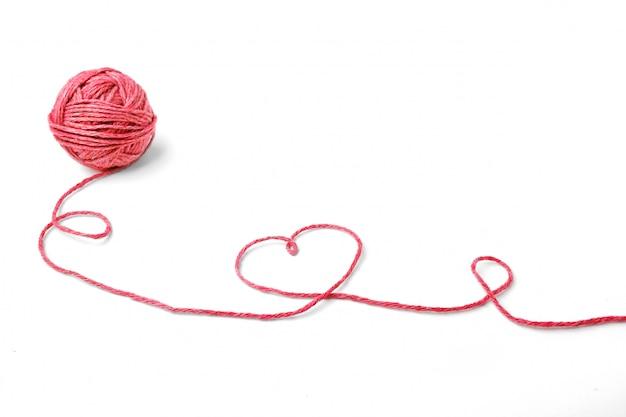 Filo rosso, cuore e groviglio su bianco