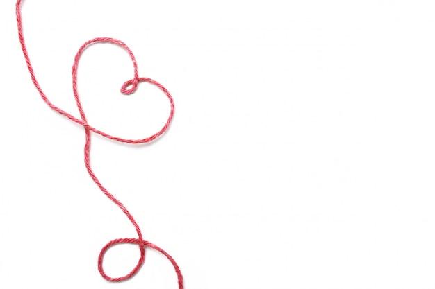 Filo rosso e cuore isolati su bianco