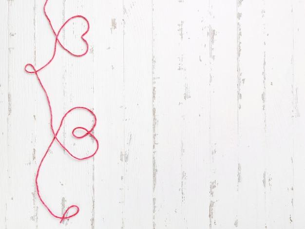 Filo rosso e due cuori su legno chiaro