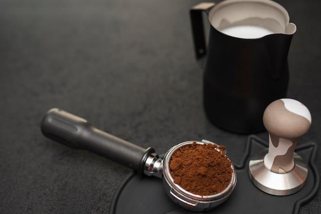 Filtro del caffè del primo piano con tamper e latte