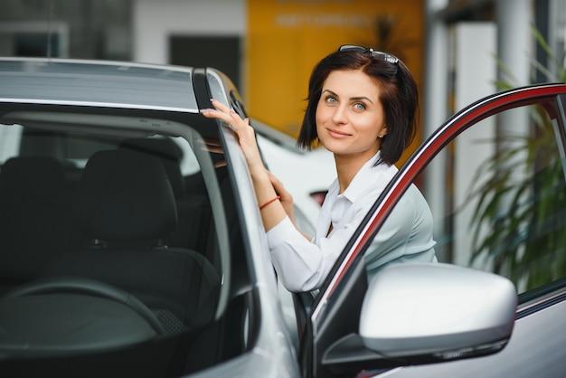 Finalmente macchina nuova! giovane cliente femminile che controlla una nuova automobile presso la concessionaria auto scegliendo decisione di acquisto acquisto consumismo sicurezza concetto di trasporto del veicolo