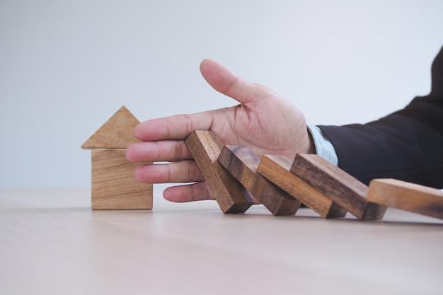 Finanza di protezione dal concetto di effetto domino. le mani fermano l'effetto domino prima di distruggere casa.