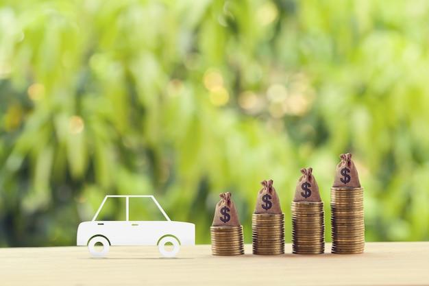 Finanza e prestito auto, rifinanziamento, rimborso in contanti, investimenti e concetto di business: modello di auto berlina modello e file di monete in aumento con sacchi di dollari usa.
