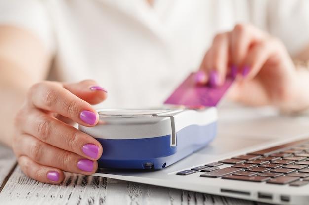 Finanza, soldi, tecnologia, pagamento e concetto della gente - vicino su della mano che inserisce la carta di credito al terminale
