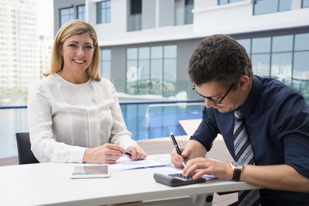 Finanziere femminile maturo emozionante allegro che sorride mentre ragioniere che per mezzo del calcolatore
